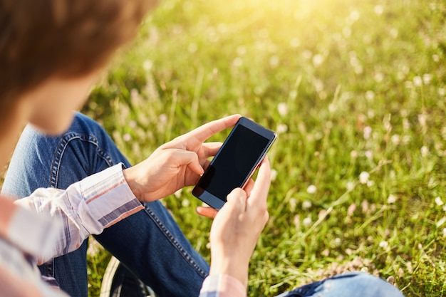インターネットやメッセージの閲覧公園で緑の芝生に座って現代のスマートフォンを保持している10代の学生少年のショットをトリミング