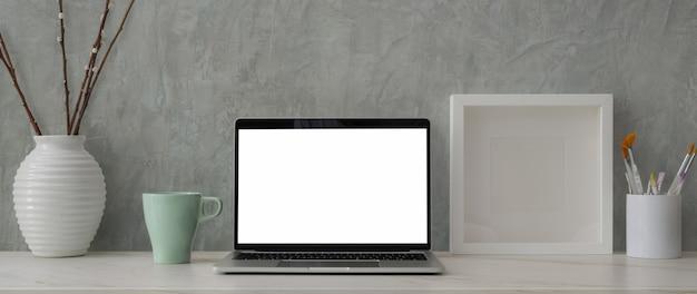 Обрезанный снимок модного рабочего пространства с ноутбуком, кистью для рисования и украшениями на мраморном столе