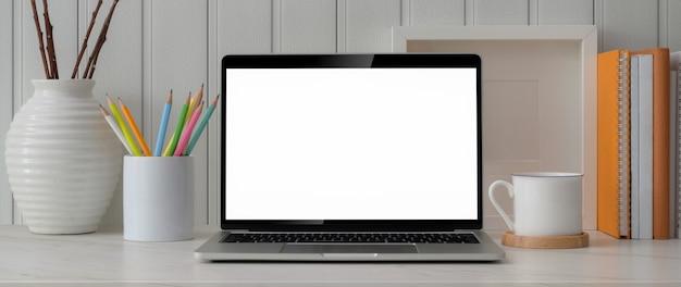 Обрезанный снимок модного рабочего пространства с ноутбуком, канцелярскими принадлежностями и украшениями на мраморном столе