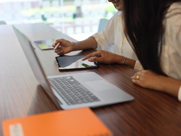 Обрезанный снимок двух женщин, смотрящих на цифровой планшет и разговаривающих друг с другом во время работы в конференц-зале