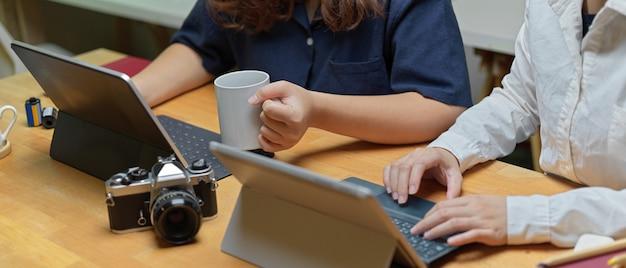 Обрезанный снимок двух женщин-партнеров, работающих вместе с цифровыми планшетами и камерой