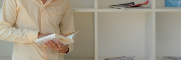 Обрезанный снимок студента университета, читающего книгу