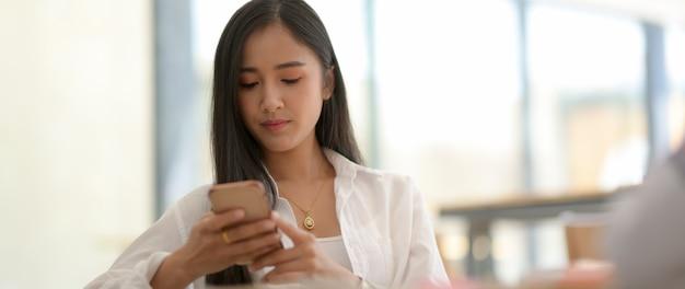 大学生のクロップショットはスマートフォンでリラックスして少し時間がかかります