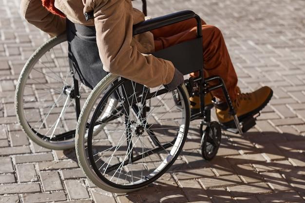 Обрезанный снимок неузнаваемого афроамериканца в инвалидной коляске, движущегося в городском городе, освещенном солнечным светом, с копией пространства
