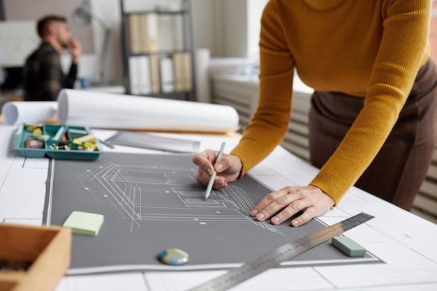사무실에서 책상에서 일하는 동안 청사진과 계획을 그리는 인식 할 수없는 여성 건축가의 자른 샷,