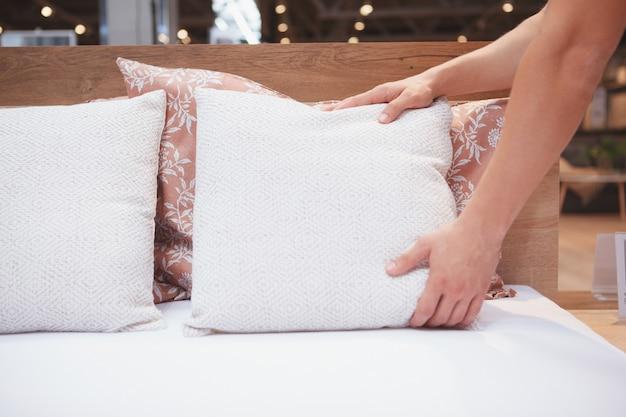 ベッドを作っている認識できない男のクロップドショット