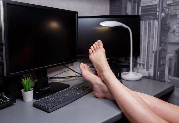 自宅の椅子に座って、ラップトップコンピューターを使用し、webを閲覧し、温かい飲み物を飲んでいる、認識できない男性のクロップドショット。自己隔離期間中に在宅勤務。ビジネス、リモートワーク