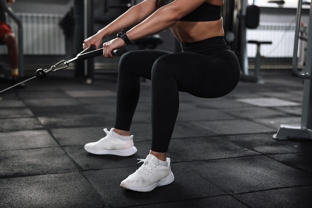 Обрезанный снимок неузнаваемой спортсменки с подтянутым сексуальным телом, сидящей на корточках в кроссовере