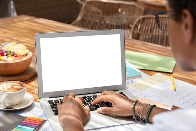 Обрезанный снимок неузнаваемой женщины печатает текст электронного письма, просматривает новости в интернете