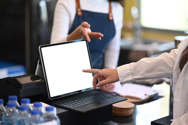 Обрезанный снимок официанта, который рекомендует и принимает заказы от клиентов в современном ресторане или кафе.