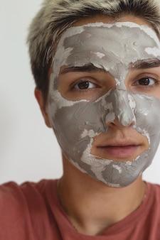 Обрезанный снимок женщины, применяющей серо-зеленую глиняную маску для ухода за кожей лица, ежедневный уход за кожей лица