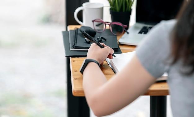 Обрезанный снимок женщины рука ручка и писать на ноутбуке, сидя за столом и работая с портативным компьютером, вид сзади с копией пространства.