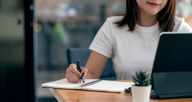 自宅のテーブルで座ってラップトップで作業しながら、ノートにペンで書いている女性の手のトリミングされたショット。