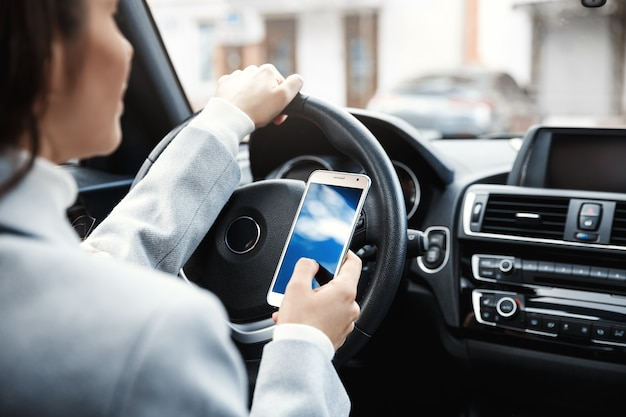 Обрезанный снимок руки женщины, держа колесо и смартфон.
