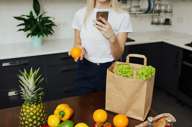 携帯電話を持ってオンラインで注文した商品をチェックしている女性のクロップドショット。