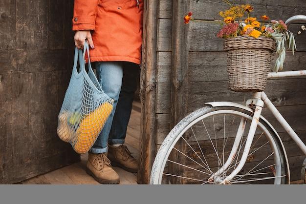 가을 제철 야채 호박, 호박, 배가 든 끈 가방을 들고 마을의 오래된 목조 주택 문에 서 있는 여성의 자른 샷, 벽에 기대어 빈티지 자전거. 가을 수확