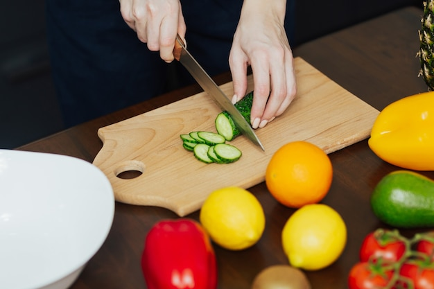 女性のクロップドショットは、キッチンで野菜サラダを準備しています。