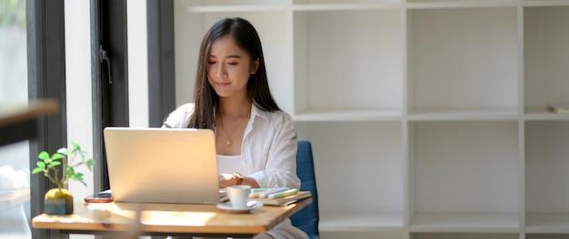 ノートパソコンでの彼女の仕事に焦点を当てた女性大学生のトリミングされたショット