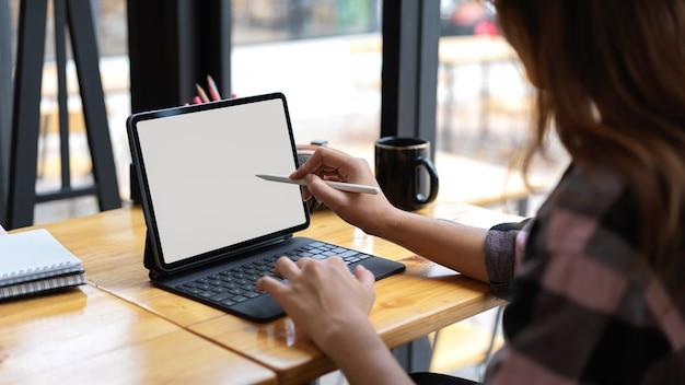 Обрезанный снимок женщины, использующей пустой экран планшета в удобном рабочем пространстве