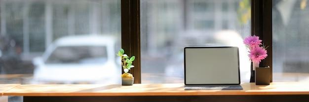 木製カウンターバーに空白の画面のタブレットと花の花瓶の作業スペースのショットをトリミング