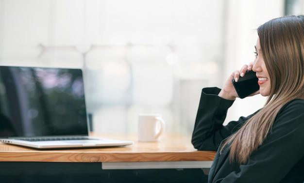 Обрезанный снимок молодой азиатской коммерсантки с помощью смартфона, сидя за своим офисным столом, вид сбоку.