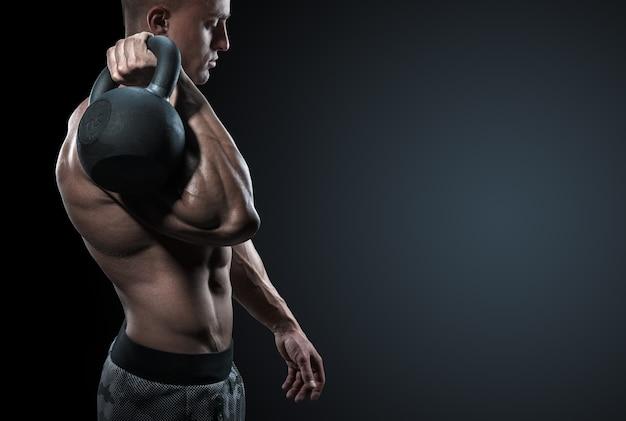 Обрезанный снимок молодого бодибилдера, держащего гирю сильный фитнес-мужчина, тренирующийся по кроссфиту с гирей в тренажерном зале