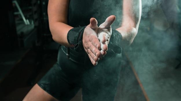 강도 훈련 전에 분필 가루로 손을 박수 젊은 여성 운동 선수의 자른 샷