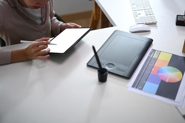若い女性のグラフィックデザイナーが顧客プロジェクトのカラーパレットで色を選択し、ワークステーションでデジタルタブレットを操作している様子のトリミングされたショット。