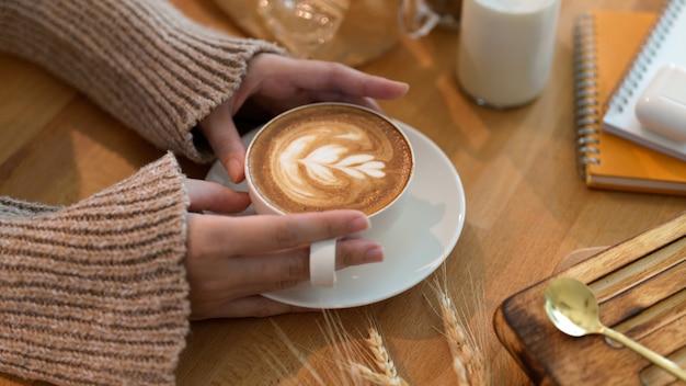 文房具と木製のテーブルでラテアートコーヒーを保持している若い女性のショットをトリミング
