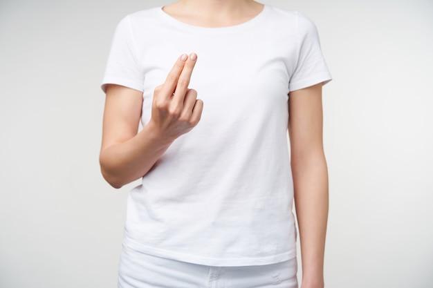 裸のマニキュアで2本の指を見せながら上げられている若い女性の手を切り取ったショット、女性は白い背景の上にポーズをとって話すために手話を学びます