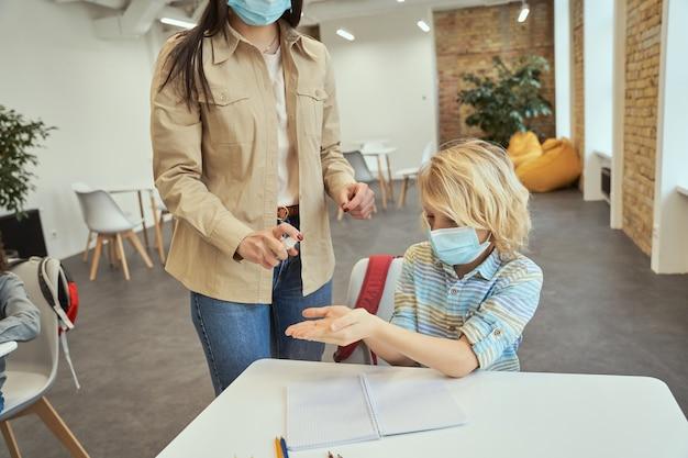 교실에서 학생 손을 소독하기 위해 알코올 스프레이를 사용하는 젊은 여교사의 자른 샷