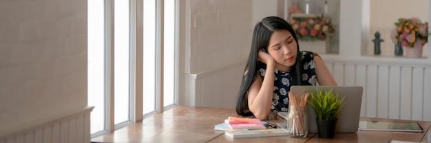 Обрезанный снимок молодой студентки, чувствующей себя уверенно, делая домашнюю работу