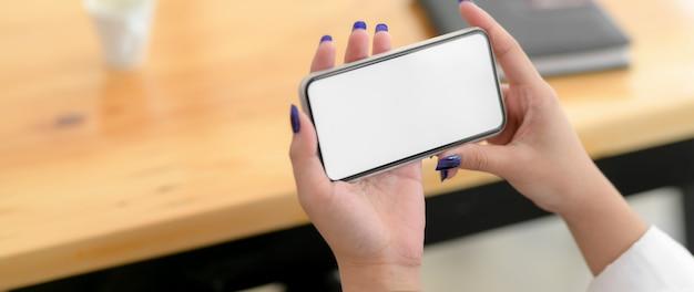 横型スマートフォンを使った若い女子大生のクロップショット