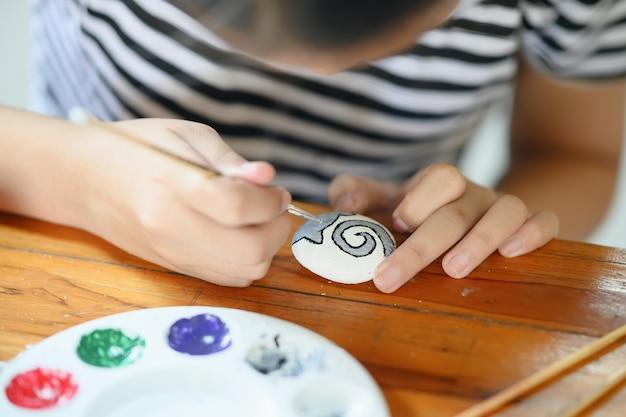 바위에 물 색으로 페인팅 어린 소녀 예술가의 자른 샷.