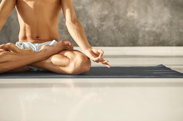 근육질 몸통과 팔을 padmasana에 앉아 mudra 제스처를 만드는 젊은 남성의 자른 샷. 로터스 포즈에서 매트에 요가 연습하는 인식 할 수없는 남자. 명상, 집중력 및 건강