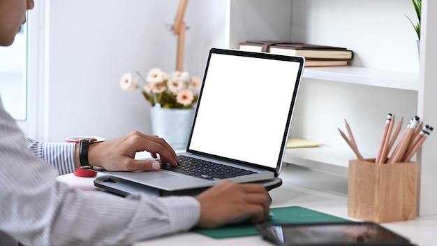 Обрезанный снимок руки молодого человека, использующего информацию поиска ноутбука на его рабочем месте в комнате домашнего офиса.