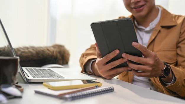 Обрезанный снимок молодого человека, читающего новости на цифровом планшете, сидя со своей кошкой в домашнем офисе.