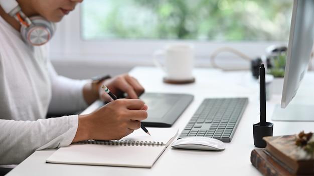 컴퓨터 앞에 앉아 노트북에 중요한 아이디어를 쓰는 젊은 남자의 자른 샷.