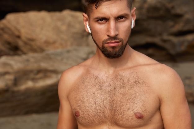 裸の体を目撃した若い筋肉ビルドマンのクロップドショット