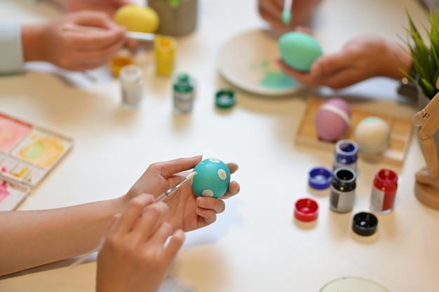 Обрезанный снимок рук молодых людей рисуют яйцо, готовясь к пасхальному фестивалю дома