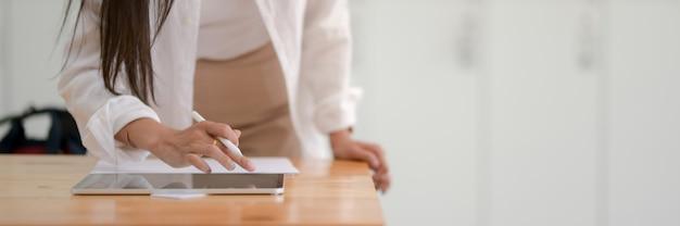 Обрезанный снимок студента колледжа молодой женщины, набрав на цифровой планшет