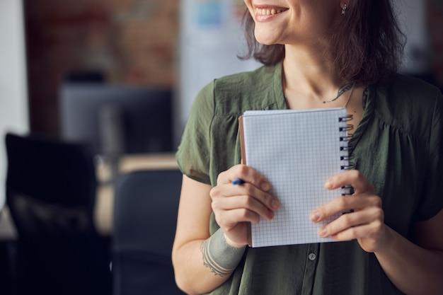 빈 공책과 펜을 손에 들고 웃고 있는 캐주얼 차림의 젊은 여성의 자른 사진