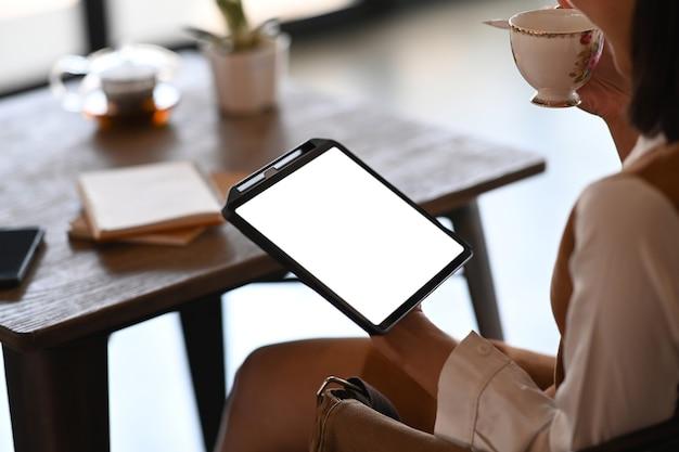 Обрезанный снимок офисного работника молодой женщины, пить кофе и с помощью цифрового планшета во время перерыва в офисе.