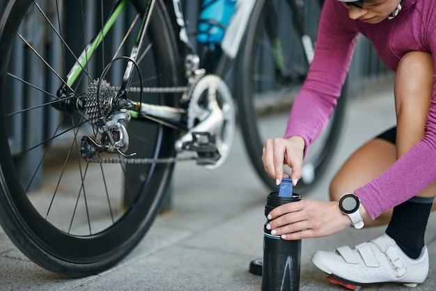 타이어를 팽창시키기 위해 펌프를 복용하는 젊은 여성 전문 여성 사이클리스트의 자른 샷