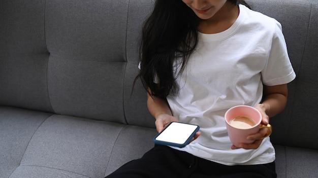 Обрезанный снимок молодой женщины, отдыхая на удобном диване с помощью смартфона и держащей чашку кофе.