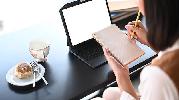 コンピューターのタブレットの前に座って日記にメモをとっている若い女性のクロップドショット。