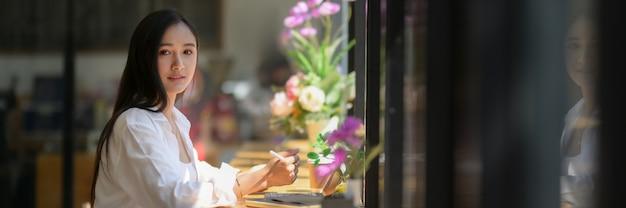 Обрезанный снимок студента университета молодой женщины, работающего над ее назначением на стойке