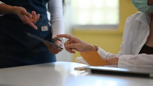 Обрезанный снимок молодой женщины в защитной маске, принимая заказ на планшете с официанткой в современном кафе.