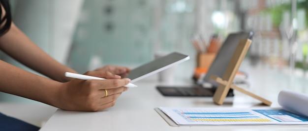 사무 용품과 현대적인 사무실 방에서 태블릿 오순절 스타일러스 펜으로 작업하는 젊은 여자의 자른 샷