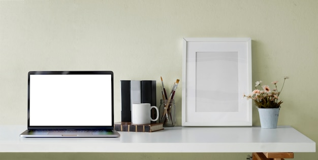 Cropped shot of open blank screen laptop computer with office supplies and  frame